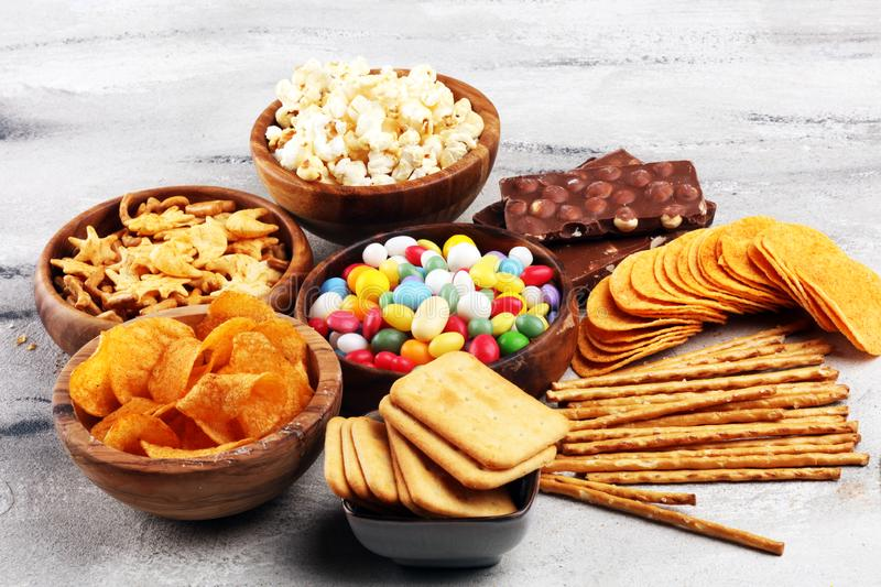 Salty snacks. Pretzels, chips, crackers in wooden bowls and candy and chocolate on table royalty free stock images