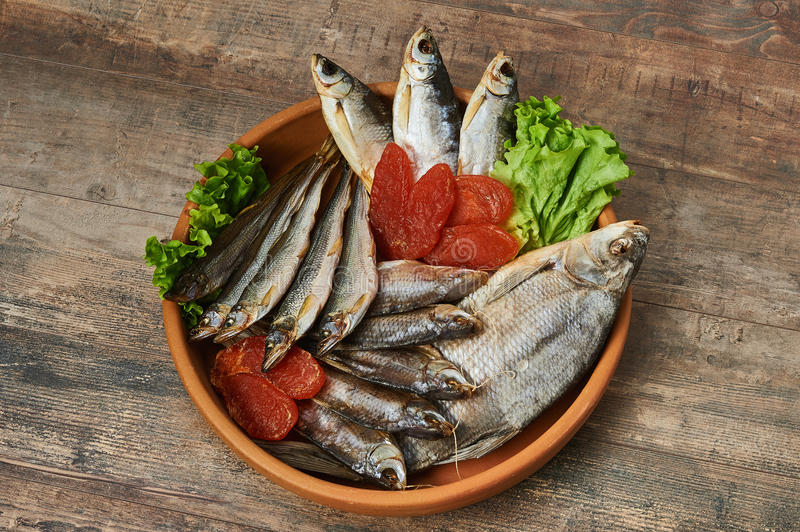 Salty stockfish on wooden table. Rainbow smelt, Common bream, Vobla, Shemay, Macrourus caviar and lettuce leaves royalty free stock image