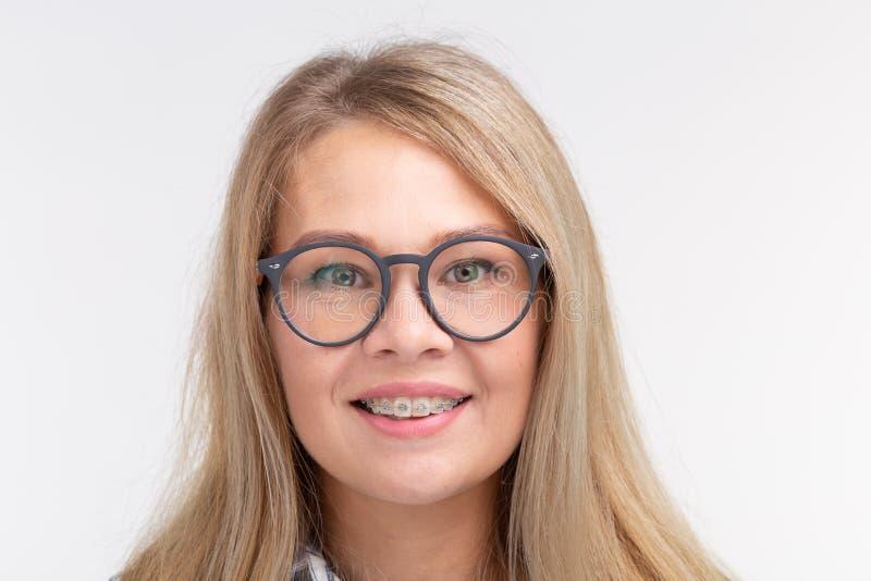 Salud de los dientes, odontología y corrección de la mordedura - mujer sonriente feliz en vidrios con los apoyos en el fondo blan foto de archivo libre de regalías