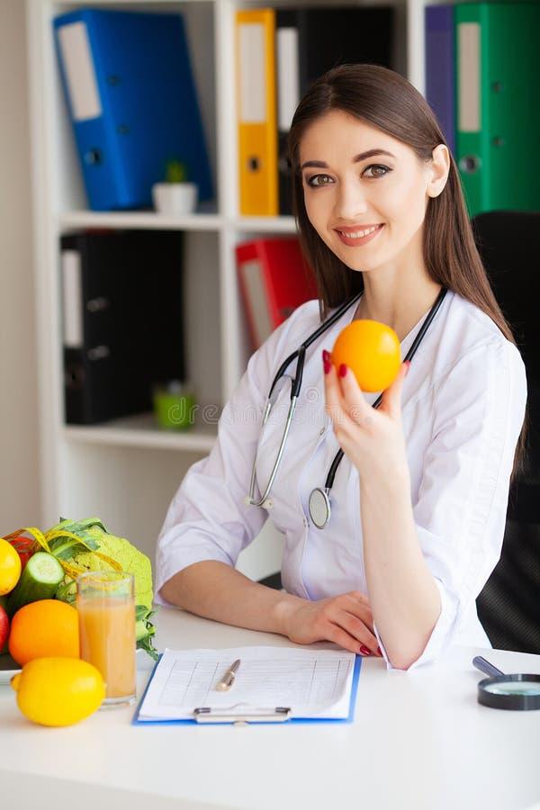 salud El doctor Dietologist Holds en las manos anaranjadas frescas Nutrición sana Verduras frescas y frutas en la tabla fotografía de archivo libre de regalías