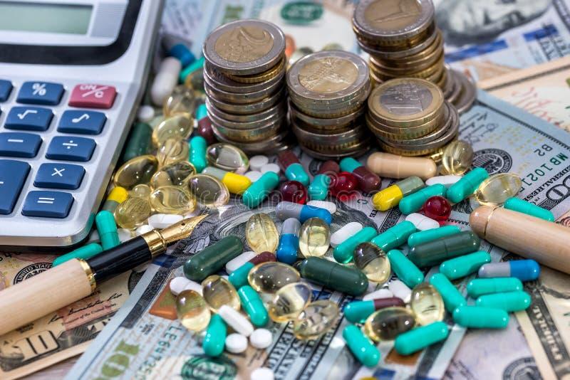 Salud, píldoras en fondo del dólar con la calculadora imagen de archivo