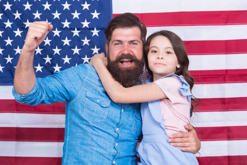 Saludar la gran bandera Familia patriótica que celebra día de la bandera con la decoración de la bandera Padre y poca hija encend foto de archivo
