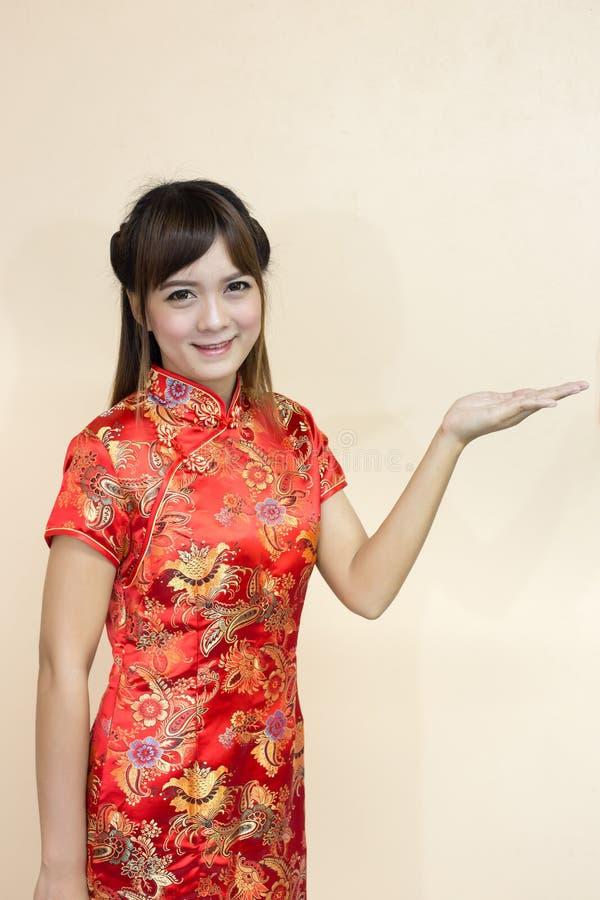 Saludo de la mujer en chino tradicional o cheongsam con la expresión de la recepción de la elevación de la mano y afortunado asiá foto de archivo