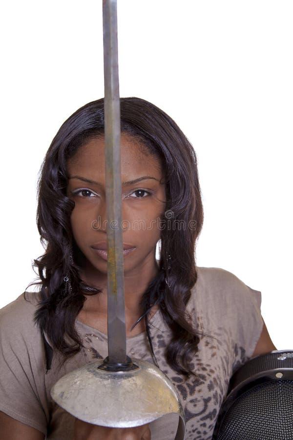 Saludo joven de la espada de la mujer negra con la máscara fotografía de archivo