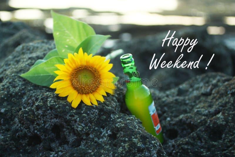 Saludos felices de las tarjetas del fin de semana, con la cerveza y girasoles hermosos que ponen en roca del mar en la playa Nota imagen de archivo