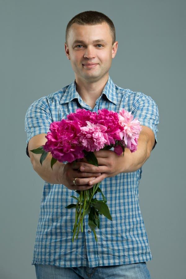 Saludos Hombre que da el ramo de flores Estilo sport enamorado hermoso joven del hombre con las flores fotos de archivo libres de regalías