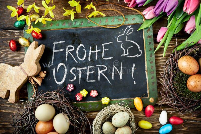 Salutation de Frohe Ostern Pâques avec des oeufs et des fleurs images stock