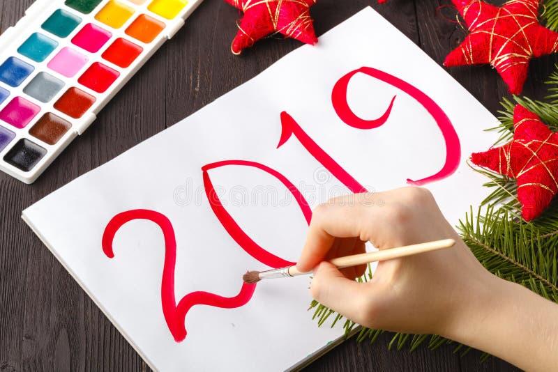Salutation peinte de Noël Enfants dessinant le symbole 2019 d'année sur le papier photo stock