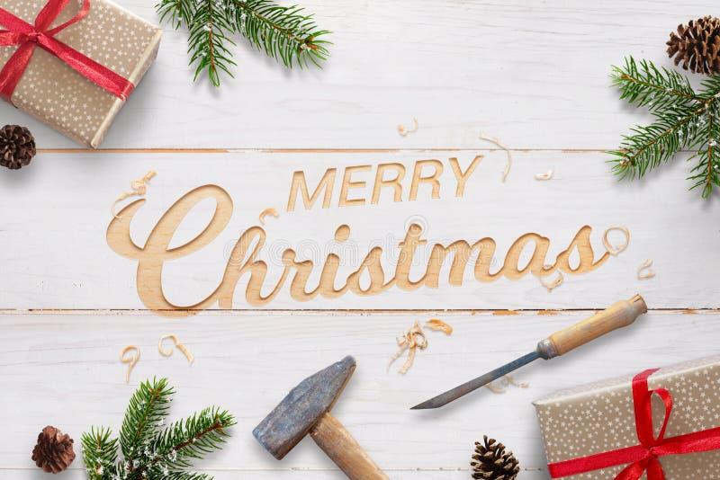 Salutation plate de Noël avec le texte découpé dans la surface en bois blanche avec le burin et le marteau photos stock