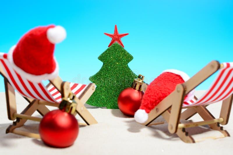 Salutations saisonnières de Noël d'une plage tropicale avec deux chaises de plate-forme, chapeaux de Santa, babioles en rouge et  images stock