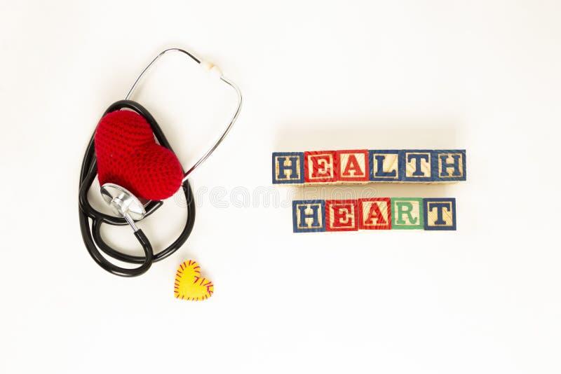 Salute del cuore e concetto di prevenzione Lo stetoscopio ed il cuore rosso di lavorano all'uncinetto su fondo isolato bianco con fotografia stock