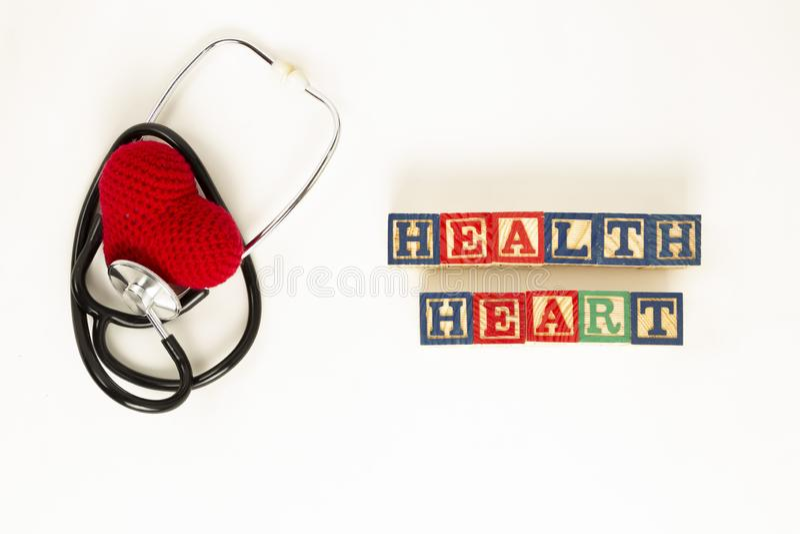 Salute del cuore e concetto di prevenzione Lo stetoscopio ed il cuore rosso di lavorano all'uncinetto su fondo isolato bianco con immagine stock