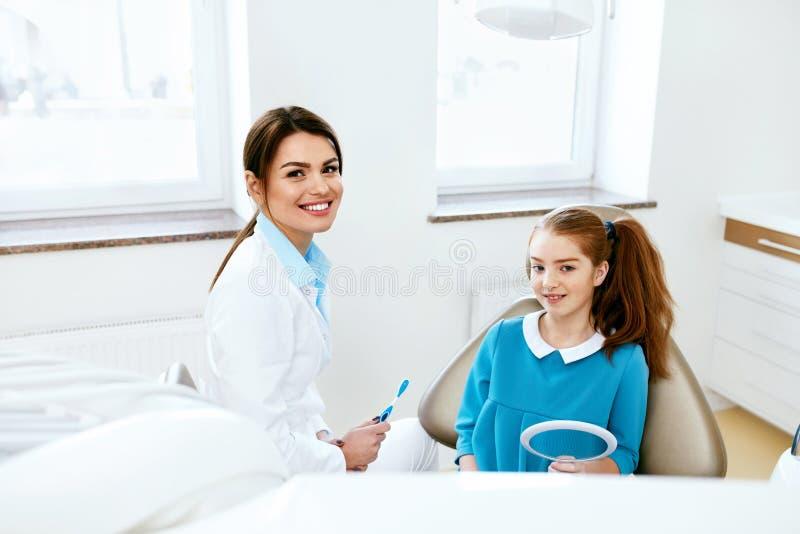 Salute dentale Dentista And Happy Girl nell'ufficio di odontoiatria immagine stock