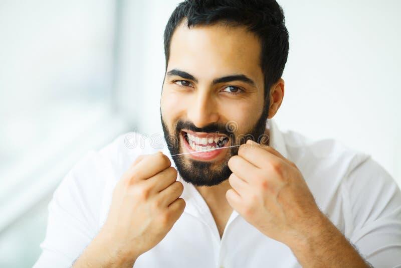 Salute dentale Uomo con il bello sorriso che Flossing i denti sani fotografie stock