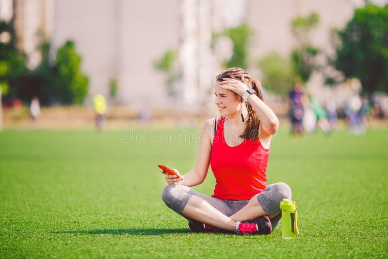 Salute di sport di tema bella seduta della ragazza che riposa sull'erba verde stadio del prato inglese facendo uso dei technodogi immagini stock