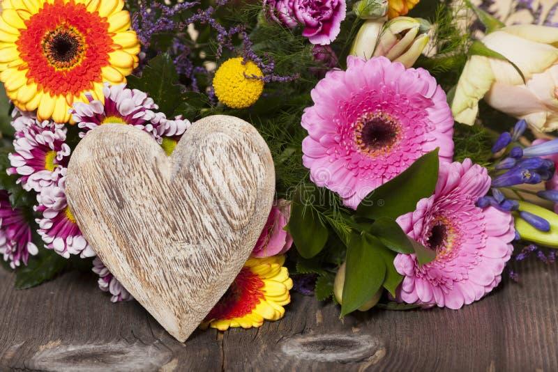 Saluti del fiore con un cuore di legno immagine stock - Modello di base del fiore ...