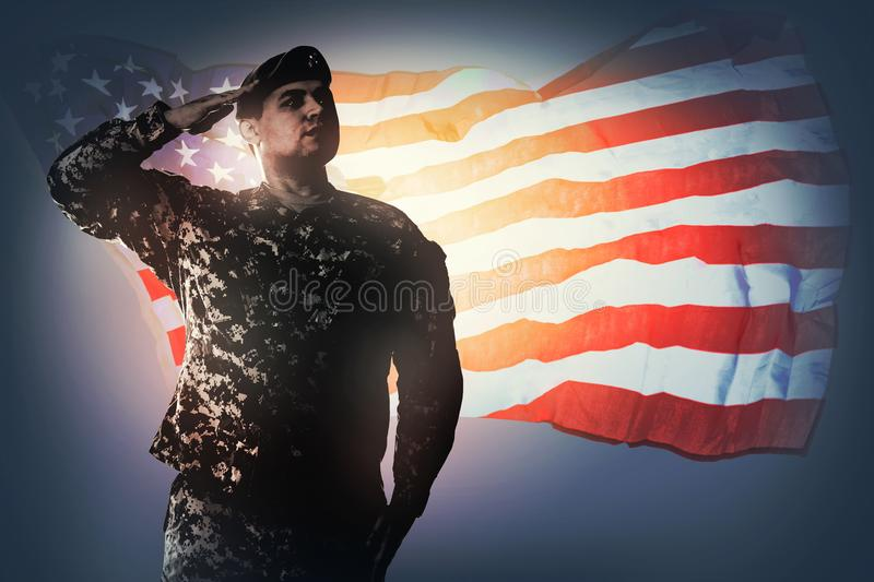 Saluting the National flag. National Anthem is played. Army Ranger from Special Troops Battalion in universal Camouflage pattern Uniforms and beret is standing stock images