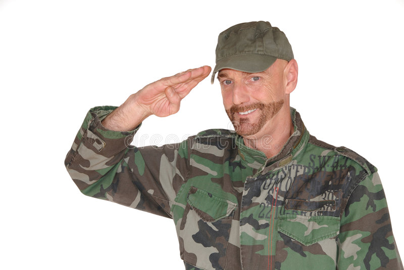 Saluting soldier. Attractive bearded middle aged smiling soldier, pride expression on face is saluting royalty free stock photography