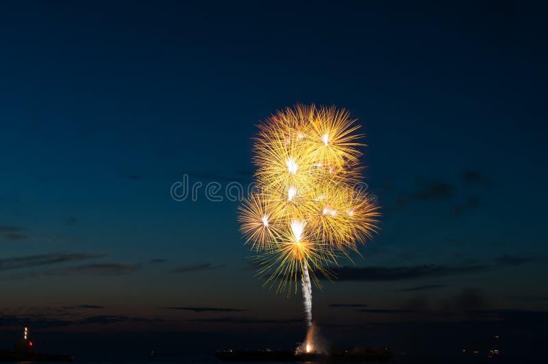 Saluto del fuoco d'artificio dorato variopinto sopra il mare immagine stock