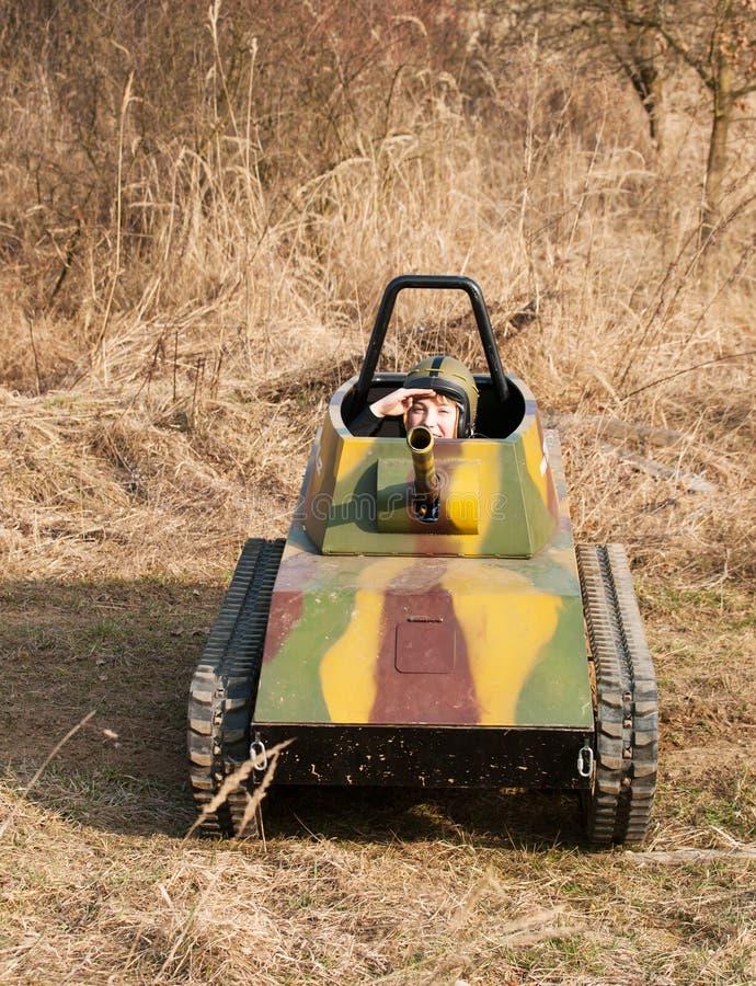 Saluto del ragazzo nel modello del carro armato immagini stock libere da diritti