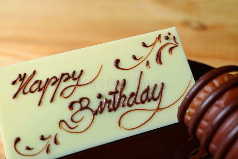 Saluto di buon compleanno scritto sulla carta fatta da cioccolata bianca completata sulla torta di compleanno del cioccolato fotografia stock