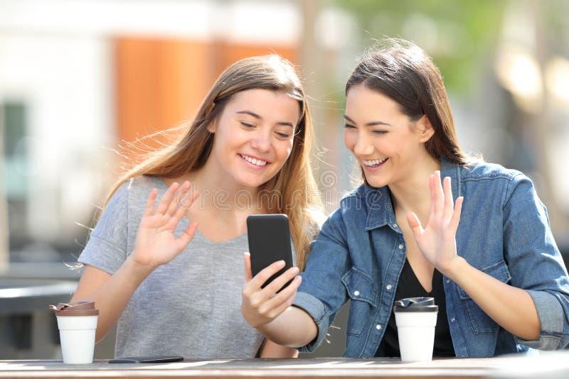 Saluto felice degli amici che ha una video chiamata sul telefono immagini stock libere da diritti