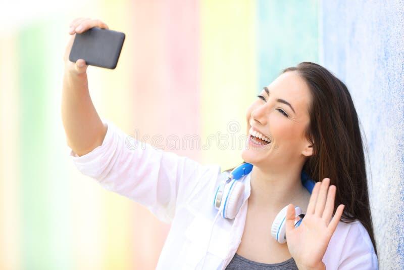 Saluto felice della ragazza che ha una video chiamata o che prende i selfies immagine stock libera da diritti