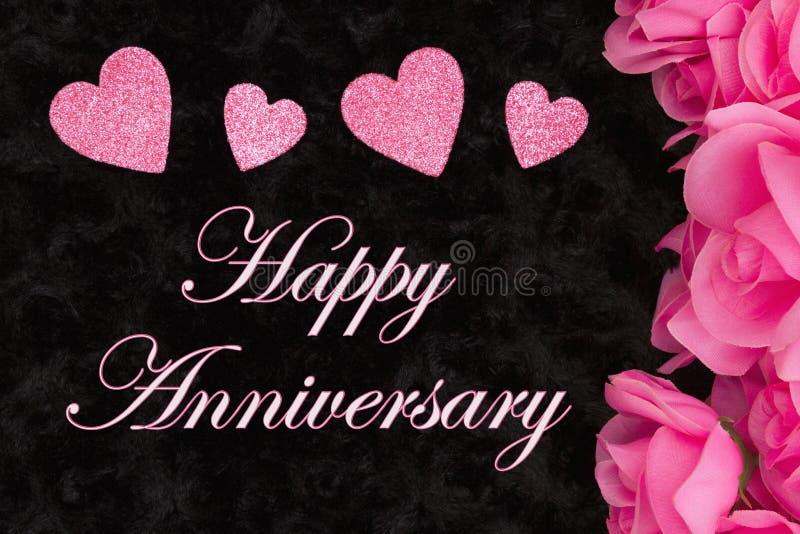 Saluto felice di anniversario con le rose rosa immagini stock