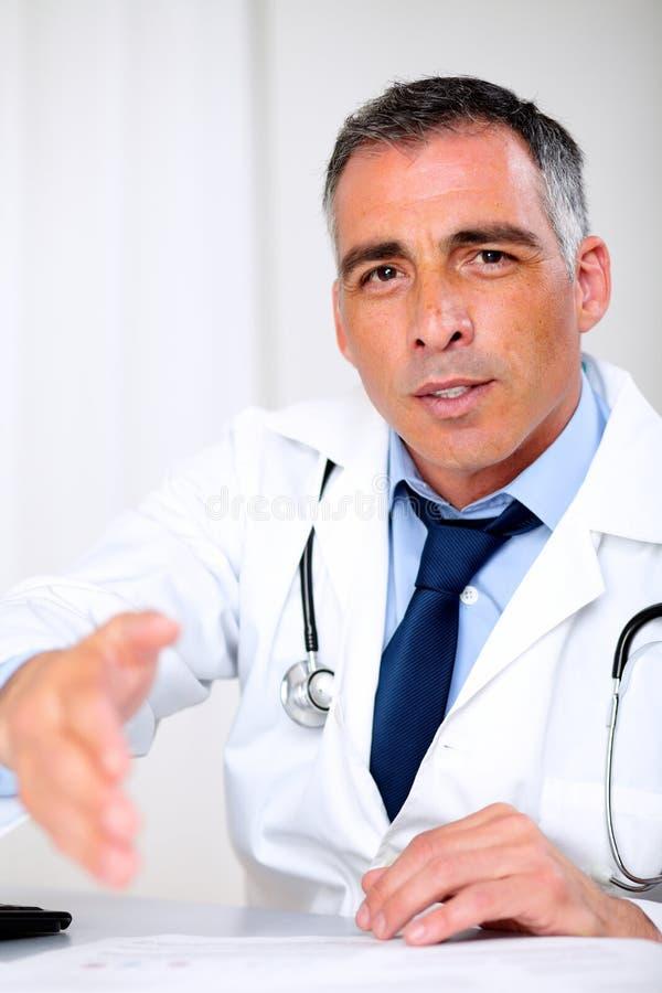 Saluto latino del medico allo scrittorio di consultazione fotografia stock
