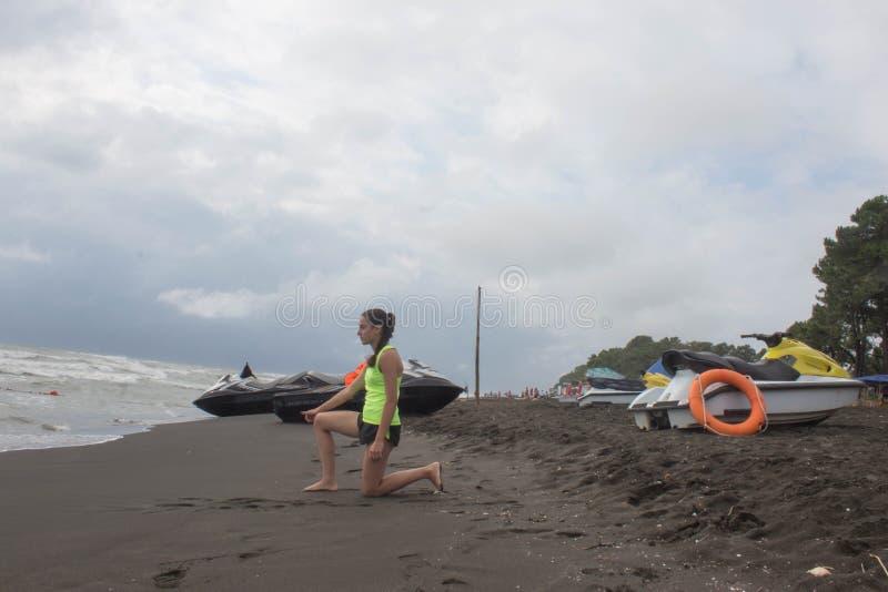 Salva-vidas da menina, com a boia alaranjada para poupanças de vida no mar de negligência do dever, praia do oceano 'trotinette'  fotos de stock royalty free