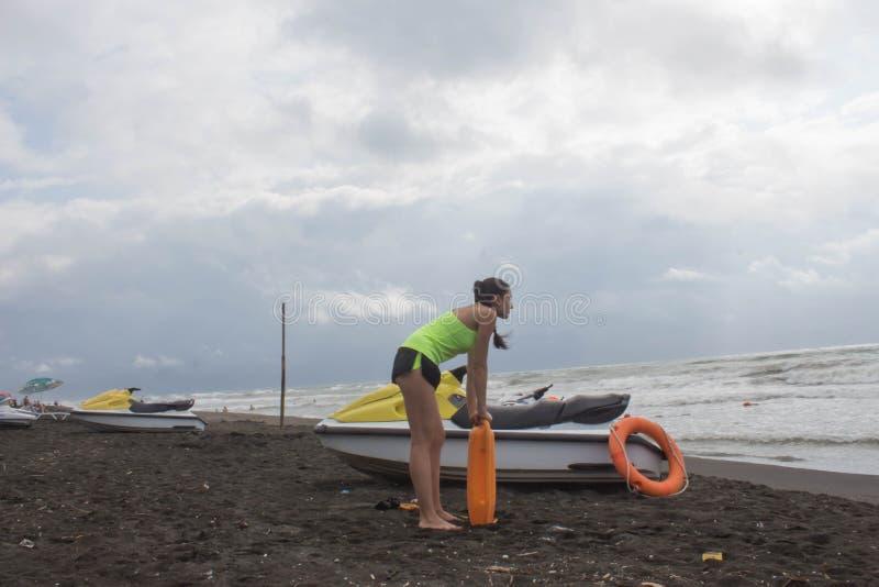 Salva-vidas da menina no dever que mantém uma boia na praia Molhe o 'trotinette', ferramenta alaranjada do conservante da equipa  imagens de stock