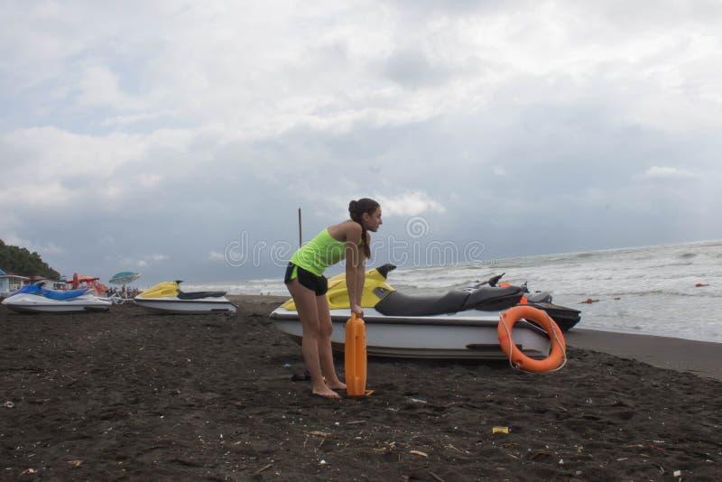 Salva-vidas da menina no dever que mantém uma boia na praia Molhe o 'trotinette', ferramenta alaranjada do conservante da equipa  foto de stock