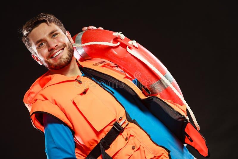 Salva-vidas na veste de vida com o boia salva-vidas da boia de anel fotografia de stock