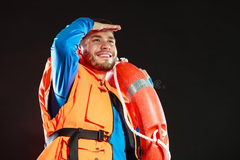 Salva-vidas na veste de vida com o boia salva-vidas da boia de anel imagem de stock