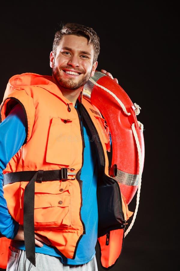 Salva-vidas na veste de vida com o boia salva-vidas da boia de anel fotografia de stock royalty free