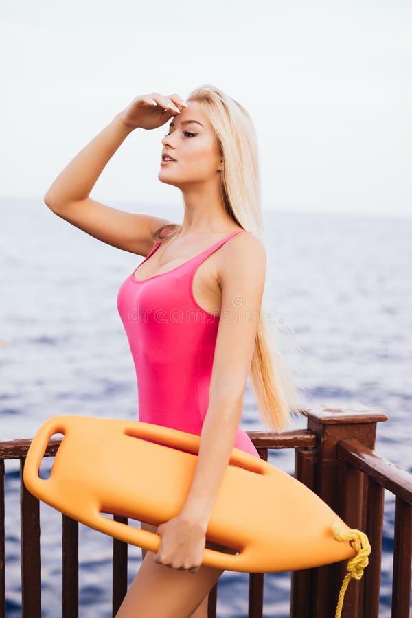 Salva-vidas 'sexy' bonita da mulher com a placa do salvamento que olha na praia no safity na água Trabalho da salva-vidas no voca imagem de stock