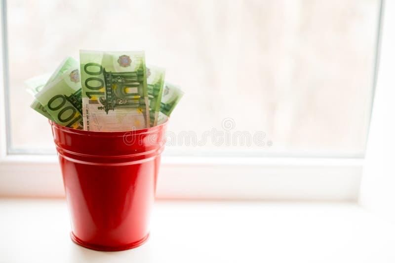 Salvadanaio, euro fattura in secchio sulla finestra bianca Fondo leggero Posto per testo Molti soldi fotografie stock libere da diritti