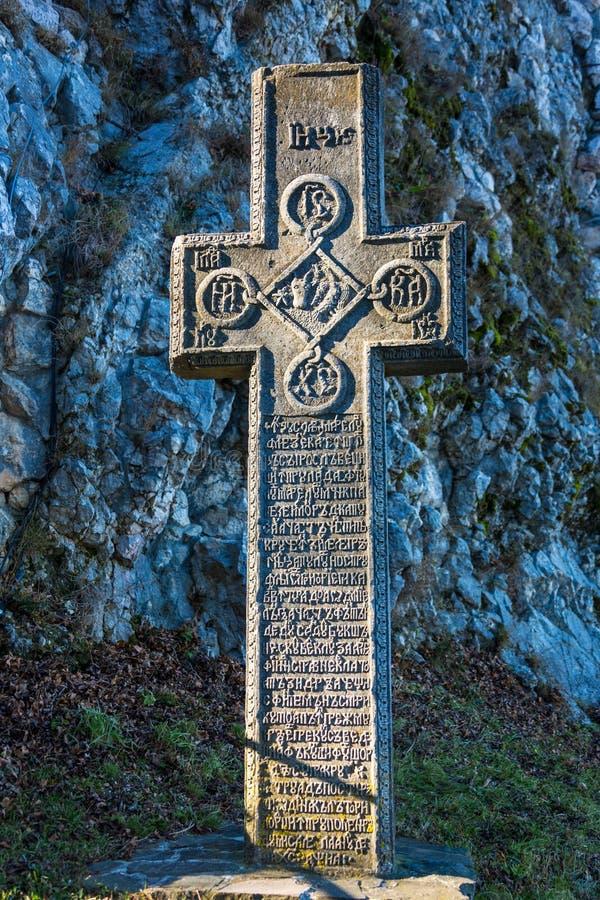 Salvado, Rumania - 19 de noviembre de 2016: Cruz de piedra medieval con símbolos religiosos en la entrada al salvado o al Drácula imagen de archivo libre de regalías