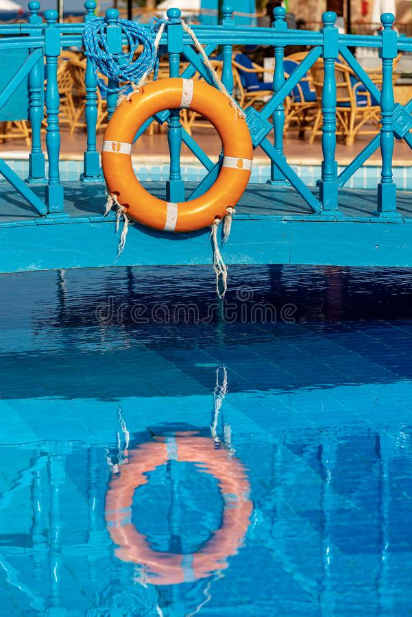 Salvagente arancio con le corde in una piscina fotografia stock