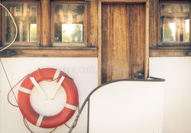 Salvagente arancio sulla barca bianca d'annata in porto immagine stock