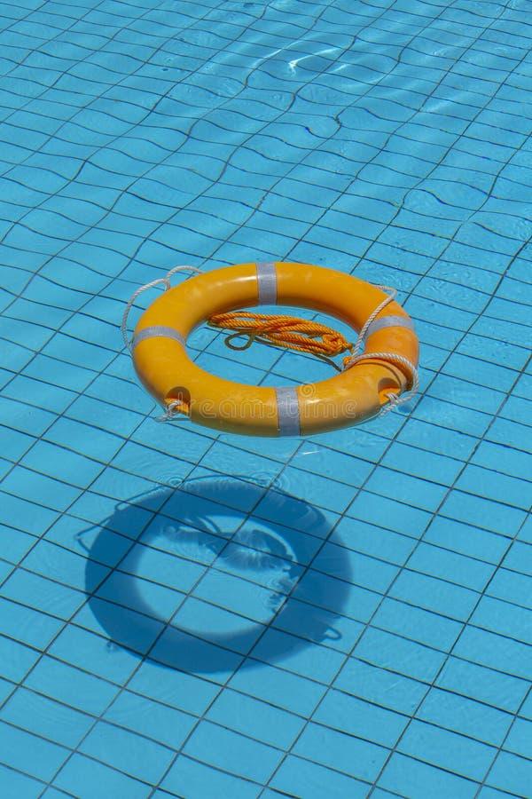 Salvagente nella piscina Concetto di vacanze estive Anello di vita che galleggia sopra l'acqua blu soleggiata immagine stock