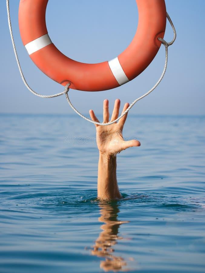 Salvagente per l'annegamento dell'uomo in acqua dell'oceano o del mare fotografia stock libera da diritti
