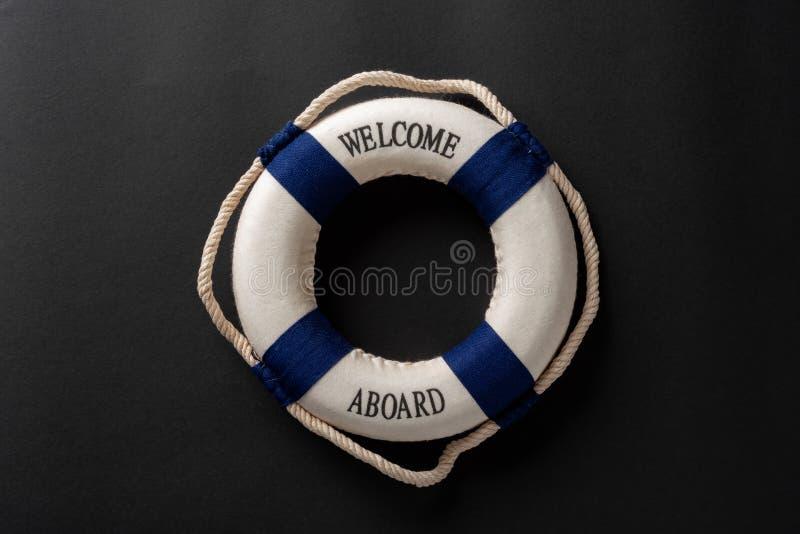 salvagente scritto con il benvenuto a bordo su fondo scuro immagini stock libere da diritti