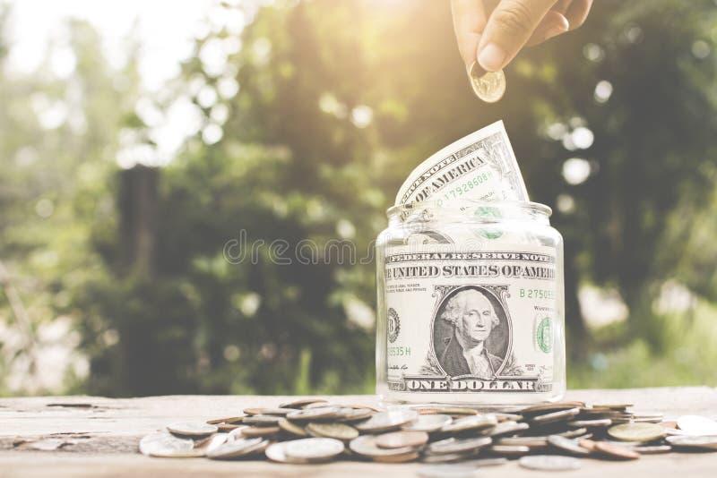 Salvar o conceito do dinheiro, mão que põe a moeda do dinheiro no frasco de vidro imagens de stock