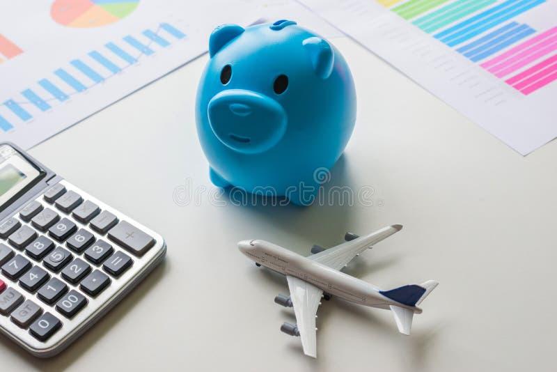 Salvar seu dinheiro para o conceito do curso Mealheiro, avião e calculadora em uma mesa branca com originais financeiros imagem de stock royalty free