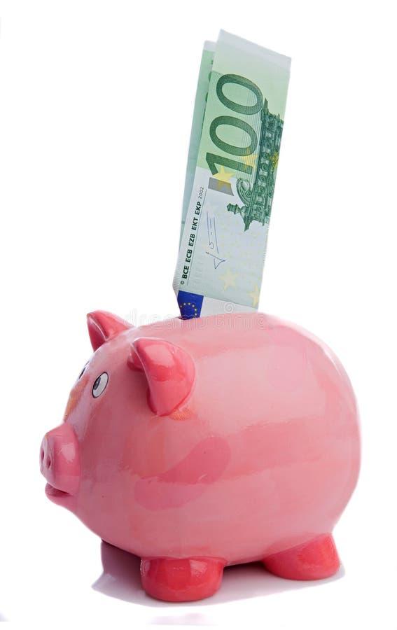 Salvare una nota di cento euro in una piggy-banca immagine stock libera da diritti
