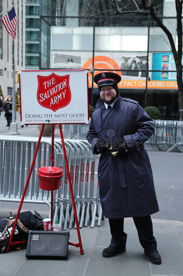 Salvation Army soldier perform for collections in midtown Manhattan. NEW YORK - DECEMBER 15, 2016: Salvation Army soldier performs for collections in midtown stock photo