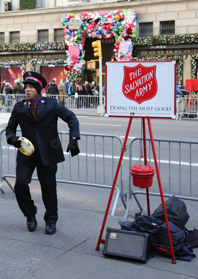 Salvation Army soldier perform for collections in midtown Manhattan. NEW YORK - DECEMBER 15, 2016: Salvation Army soldier performs for collections in midtown royalty free stock photo