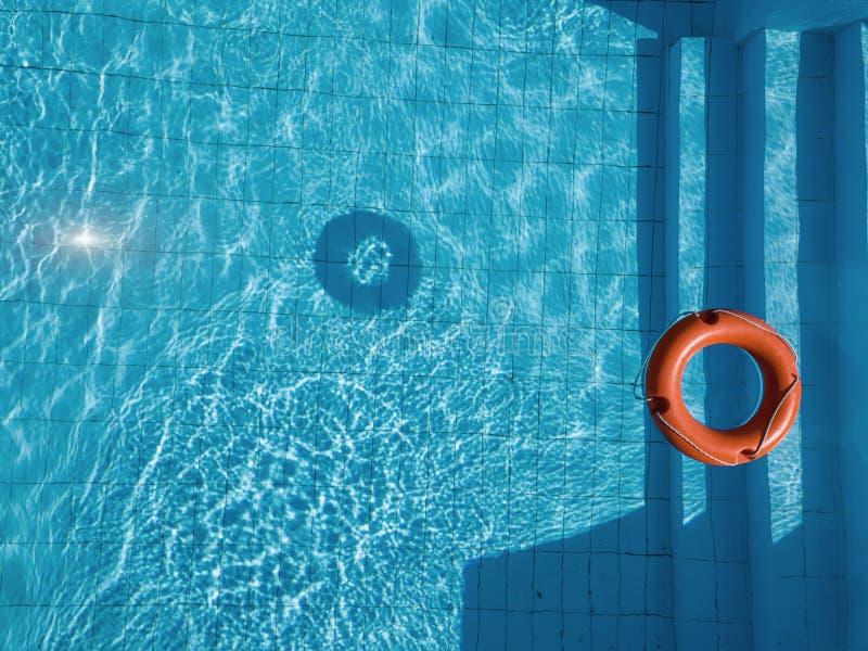 Salvavidas anaranjado en una piscina en verano fotos de archivo libres de regalías