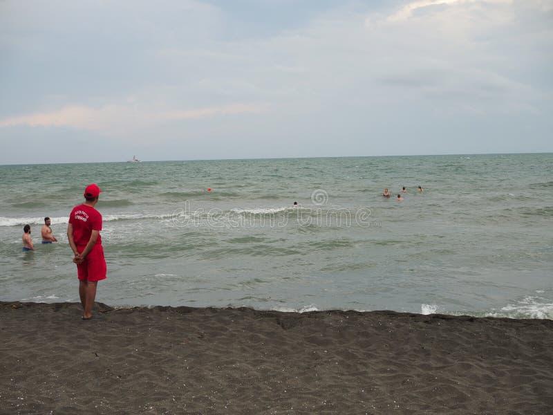 Salvavidas en la costa del mar que mira a los bañistas en la tormenta de los turistas Georgia, Ureki - junio de 2019 foto de archivo